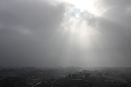 sunlight shining through thick clouds over hazy town