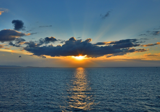 sunlight and cloud above calm sea