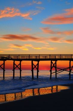 wooden bridge on calm beach at sunset