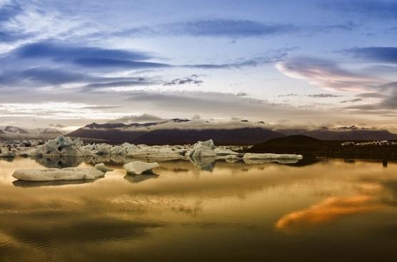 sunset icebergs water