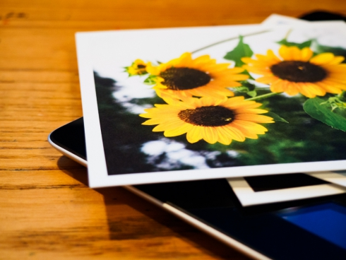 tablet with photo prints on desk