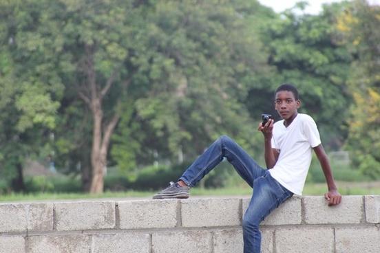 teen boy sitting on brick wall with camera