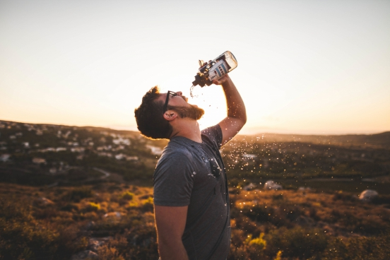 thirsty man drinking bottled water