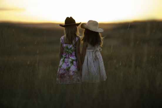 two girl standing on a field