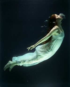 woman diving under water with white dress