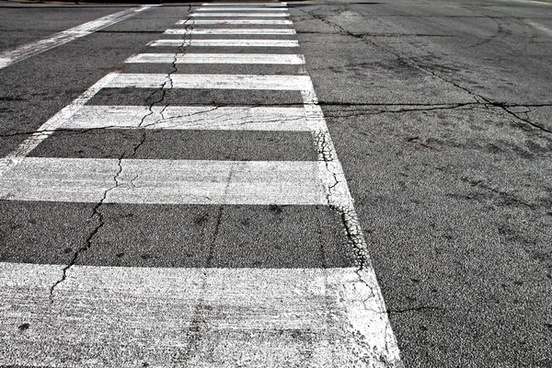 white crosswalk painted on cracked pavement