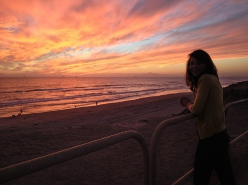 woman at the beach with sunset clouds