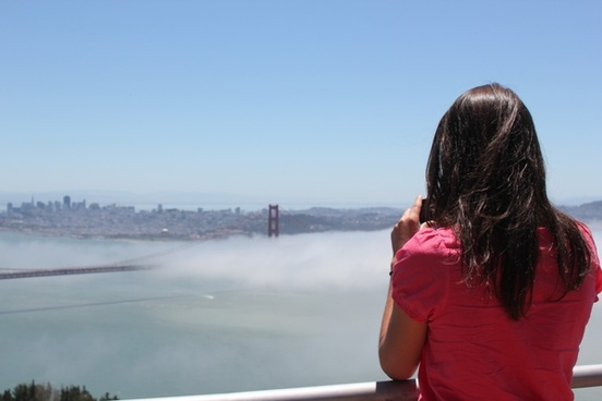 woman gazing at golden gate bridge in fog