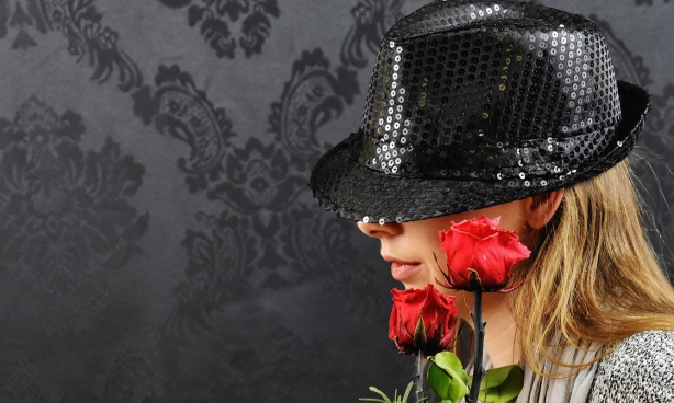 blonde woman posing with black hat and roses
