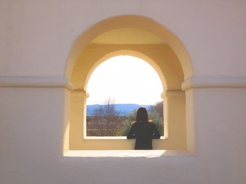 woman looking out arch window