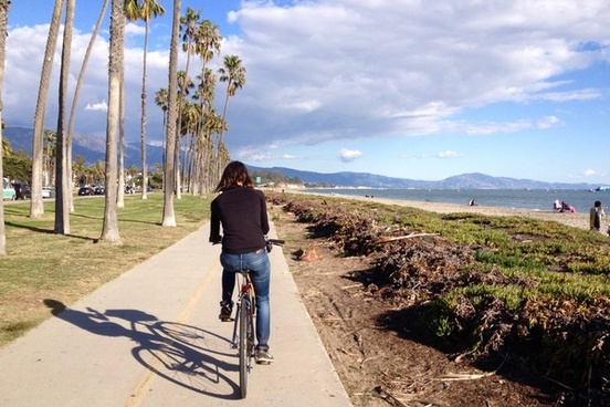 woman riding bicycle on path along beach