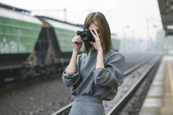 woman taking pictures at train station