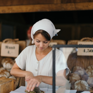 women cutting bread at her shop
