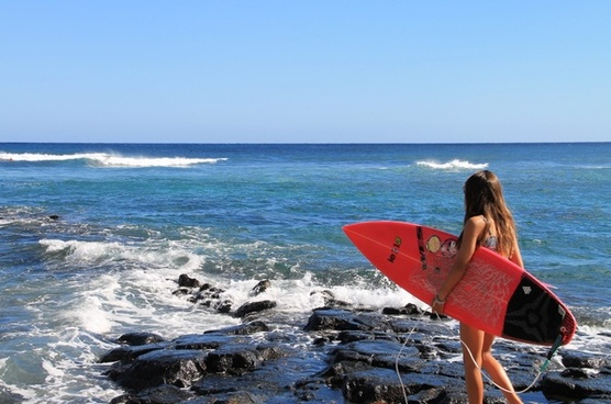 young girl holding surfboard at ocean